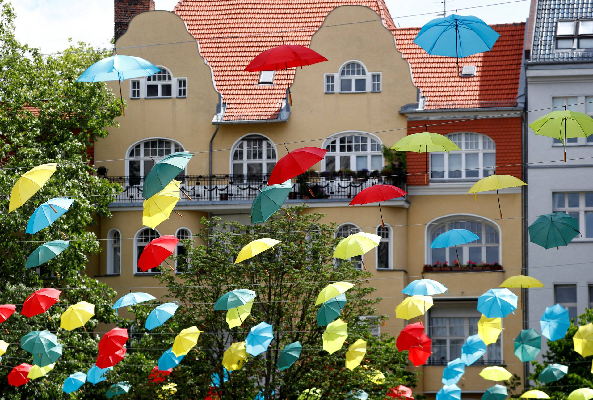Coloured umbrellas are hanging on ropes over a square to advertise an upcoming wine festival at Berlin's Charlottenburg district in Berlin