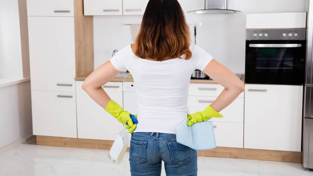 Woman Standing In Kitchen Using Cleansing Product
