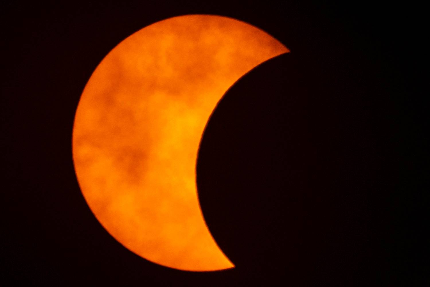 A photo shows a partial solar eclipse observed in Bangkok