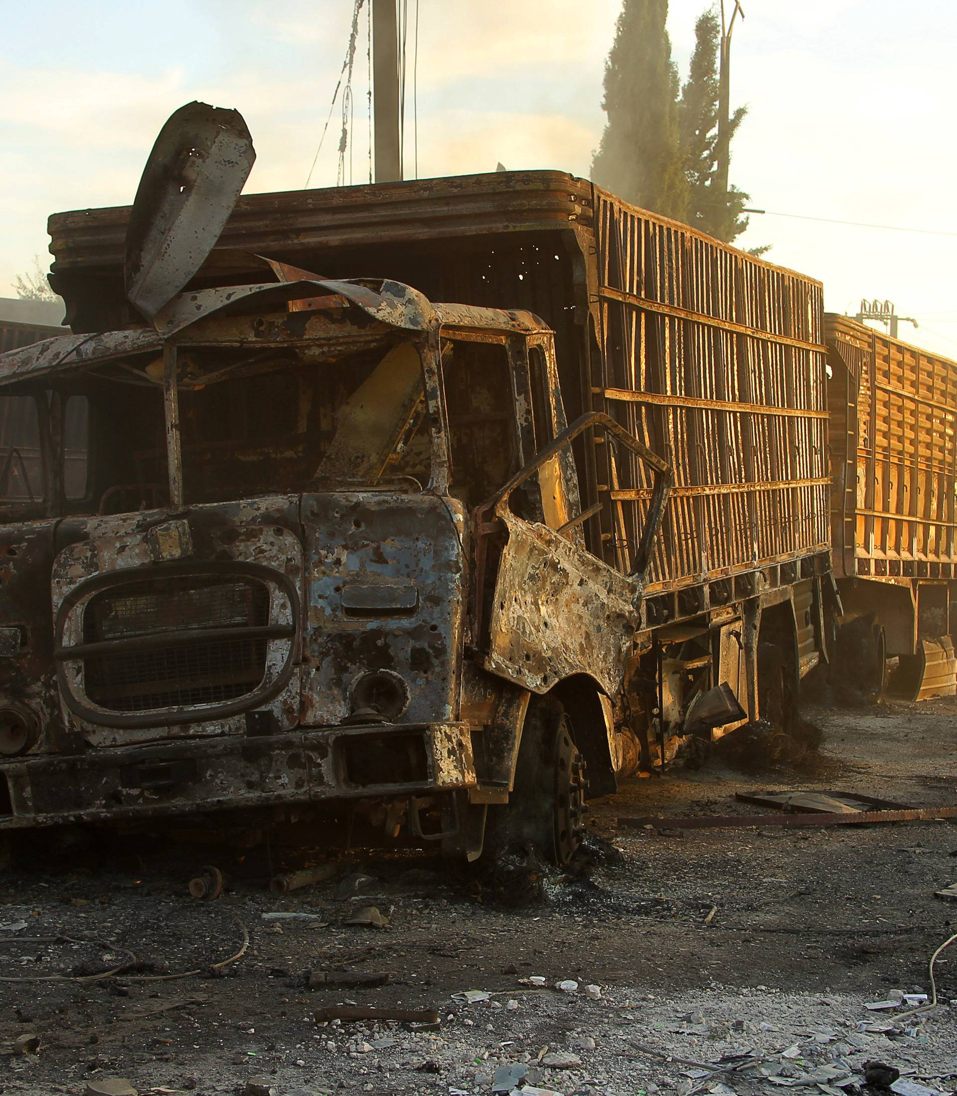 Damaged aid trucks are pictured after an airstrike on the rebel held Urm al-Kubra town