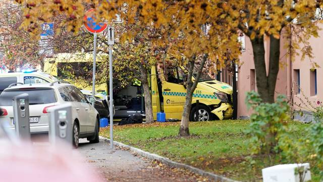 A damaged ambulance stands next to a building after an armed man who stole the vehicle was apprehended by police in Oslo