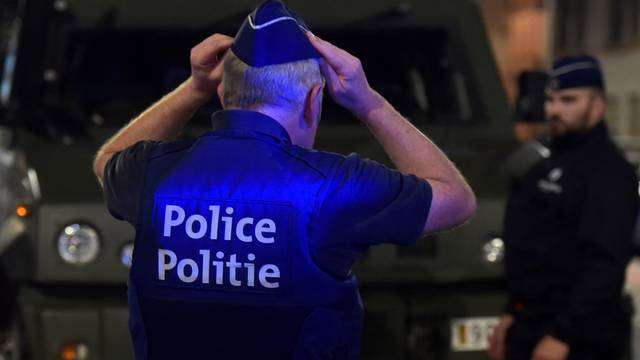 A policeman reacts on the scene after Belgian soldiers shot a man who attacked them with a knife, in Brussels