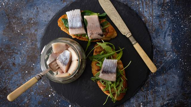 Herring sandwich (traditional Danish smorrebrod) on cutting boar