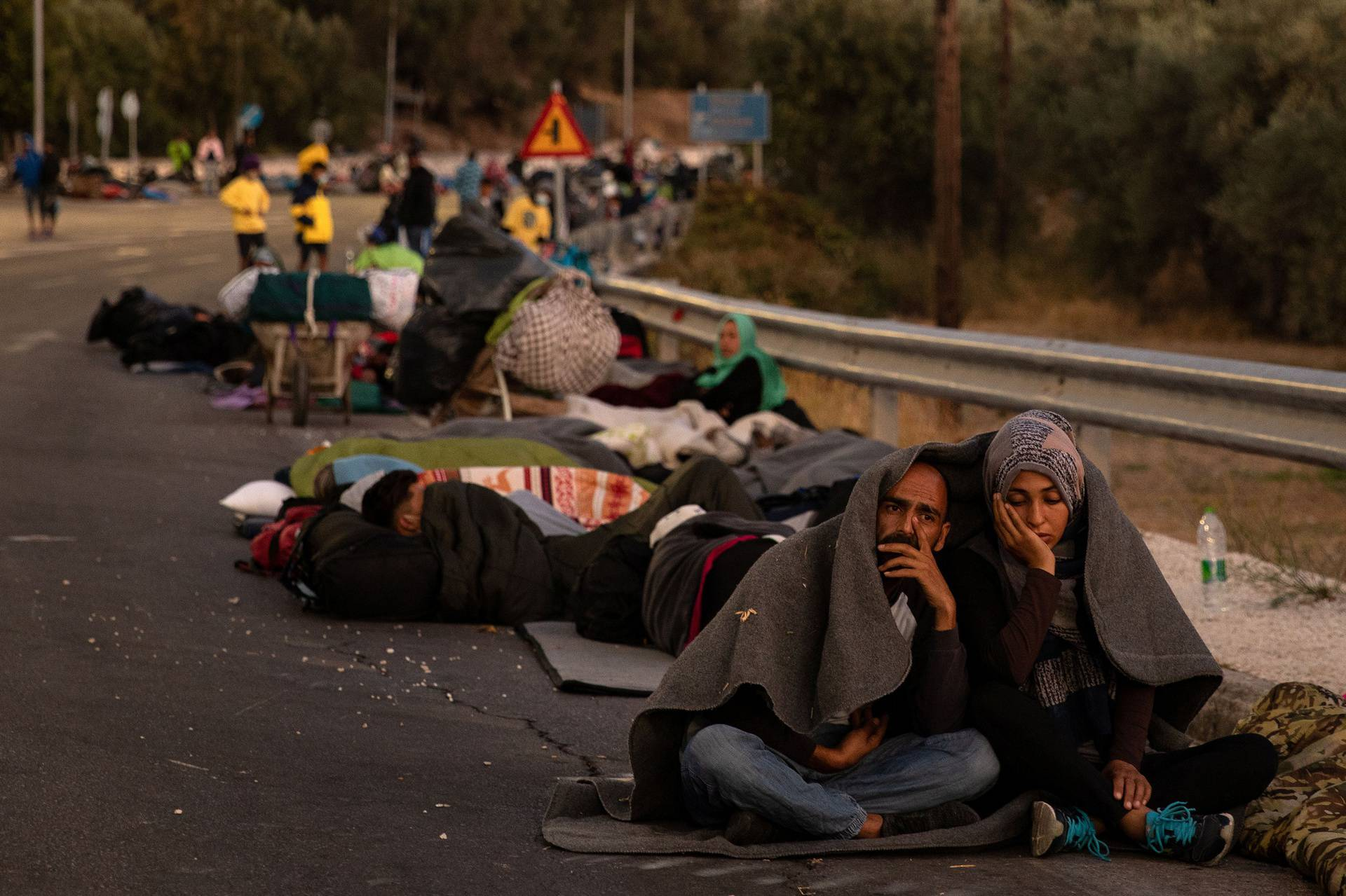 Couple sits covered with a blanket as refugees and migrants camp on a road following a fire at the Moria camp on the island of Lesbos