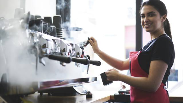 Smiling,Busty,Female,Barista,Using,Professional,Coffee,Machine,Enjoying,Job