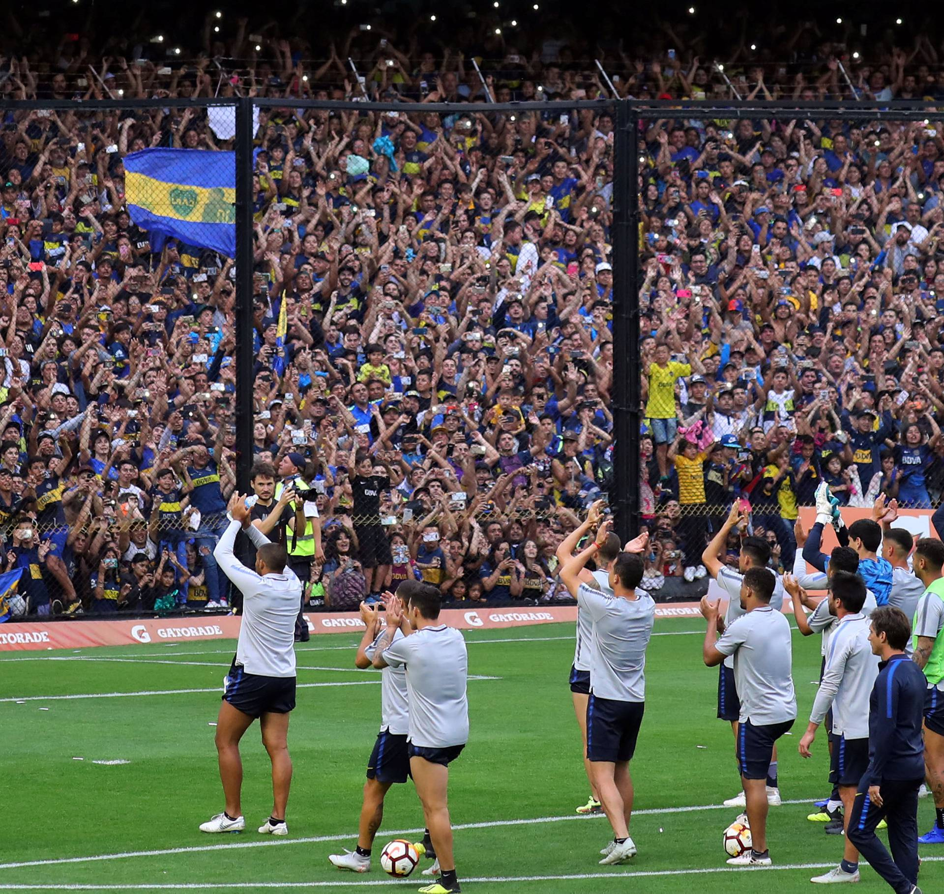 Boca Juniors' players acknowledge supporters during a training session ahead of their second leg Copa Libertadores final match against River Plate in Buenos Aires