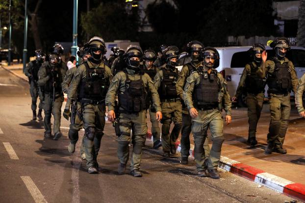 Israeli security force members patrol during a night-time curfew following violence in the Arab-Jewish town of Lod