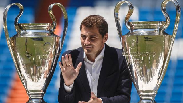 FILE PHOTO: Departing Real Madrid captain and goalkeeper Iker Casillas waves as he poses surrounded by trophies at an official send-off at the Bernabeu stadium in Madrid, Spain