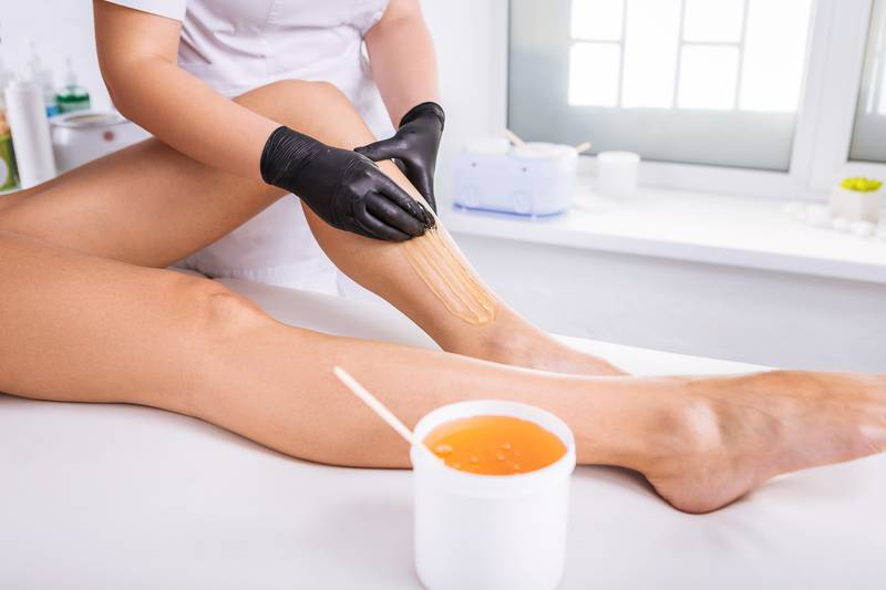 Professional master of wax depilation providing service for client