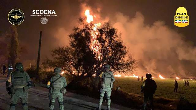 Military personnel watch as flames engulf an area after a ruptured fuel pipeline exploded, in the municipality of Tlahuelilpan, Hidalgo