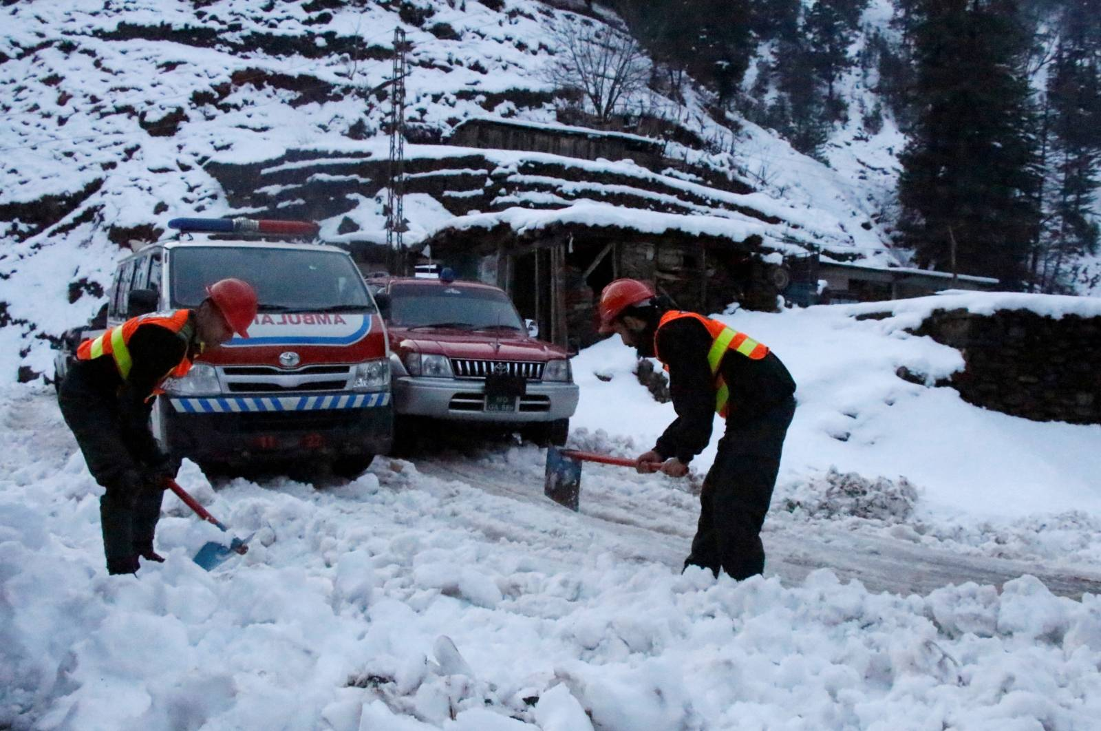 Rescue workers clear a snow-covered road to make way for an ambulance to reach the areas affected by heavy snowfall and avalanches, in Neelum Valley
