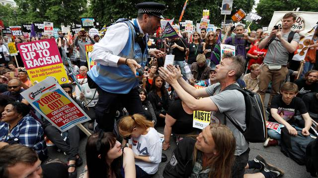 A police officer tells demonstrators to move during a sit-down protest outside Downing Street at an anti-austerity rally and march organised by campaigners Peoples' Assembly, in central London