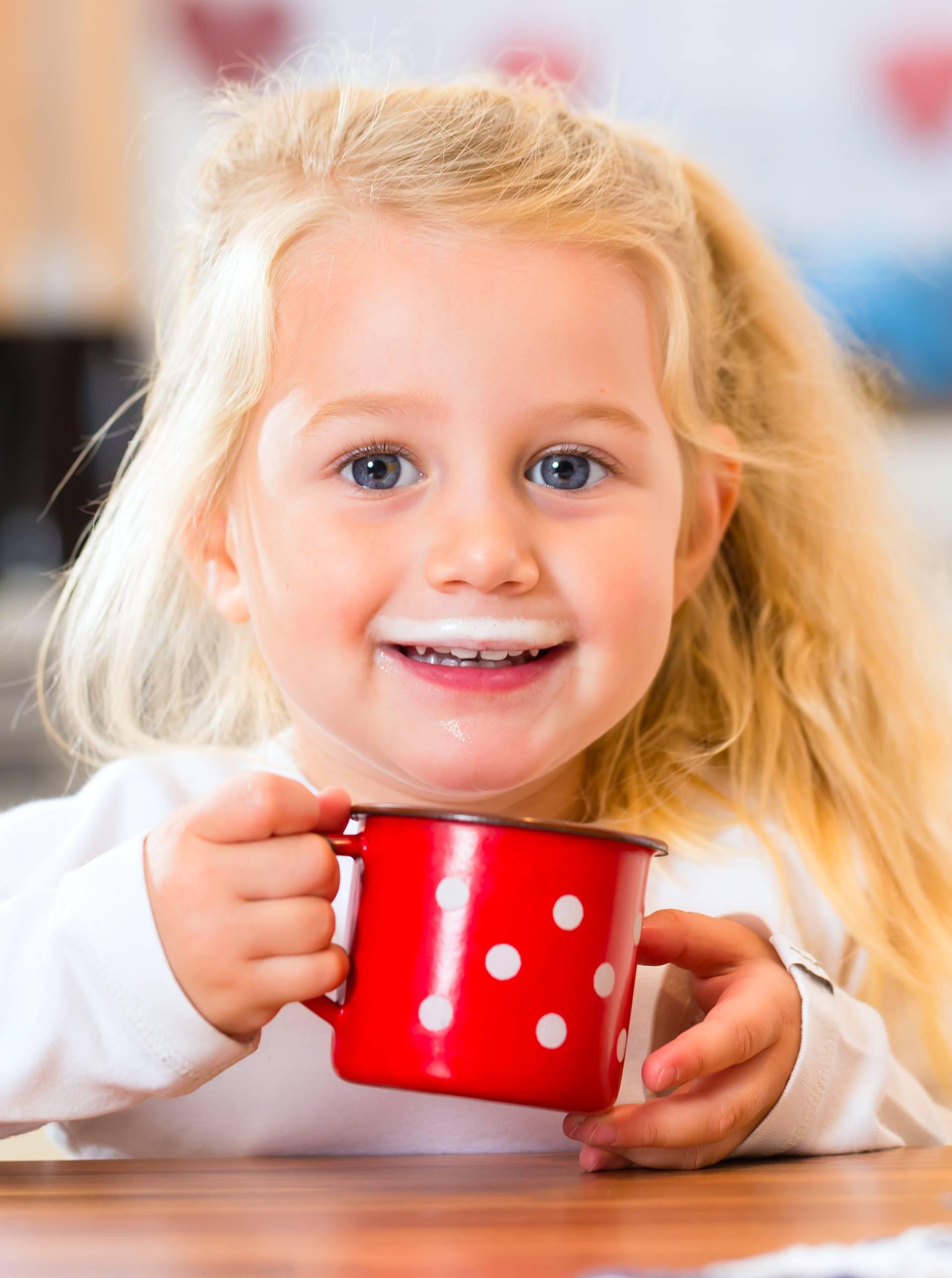 Girl drinking milk in kitchen
