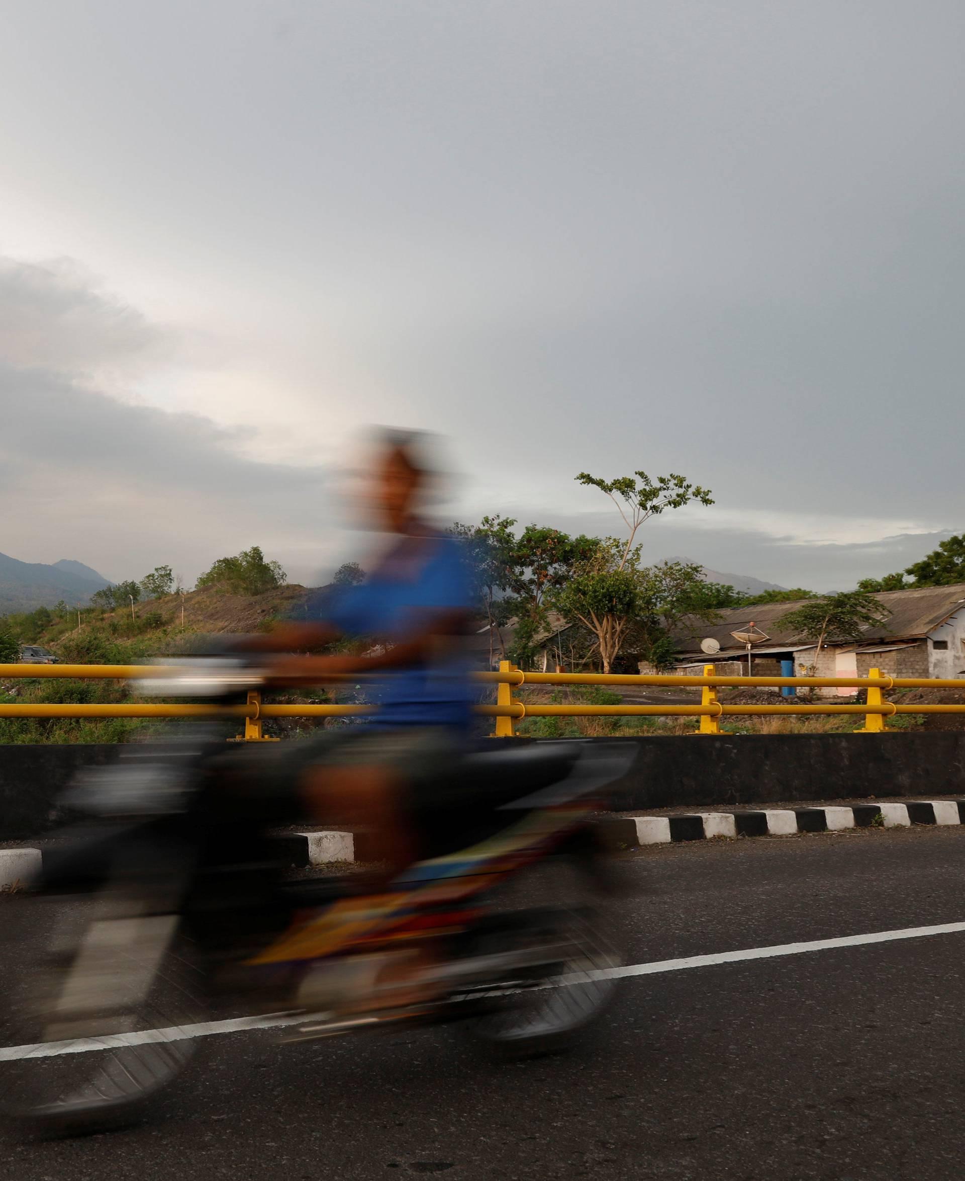 A motorist rides across a bridge as Mount Agung volcano erupts near Kubu in Bali