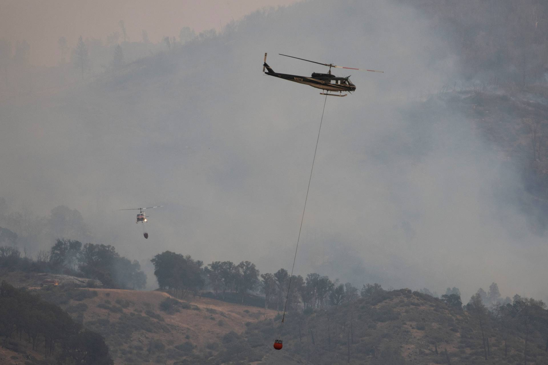 Helicopters and crew carry water to extinguish section of  LNU Lightning Complex Fire near Middletown, California