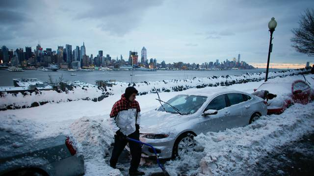 Residents clear their cars and street of snow in Weehawken, New Jersey, as the skyline of Manhattan and the Hudson River are seen after a snowstorm in New York