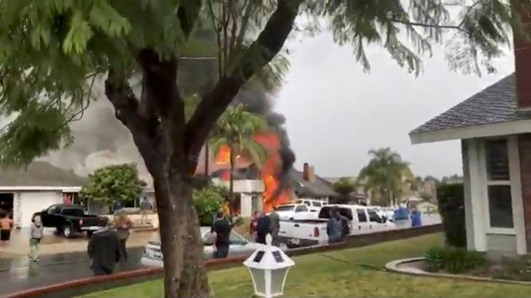 Smoke billows after a plane crashed into a house in a residential neighborhood in Yorba Linda, California