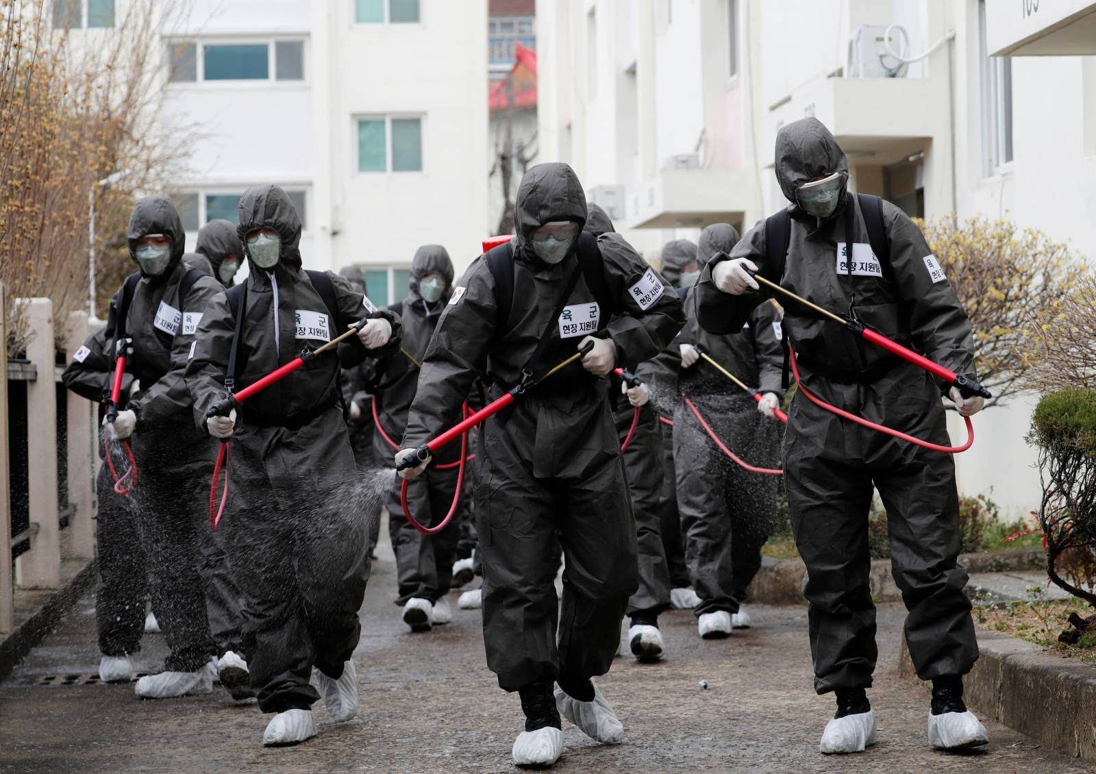 South Korean soldiers spray disinfectants inside an apartment complex which is under cohort isolation after mass infection of coronavirus disease (COVID-19) in Daegu