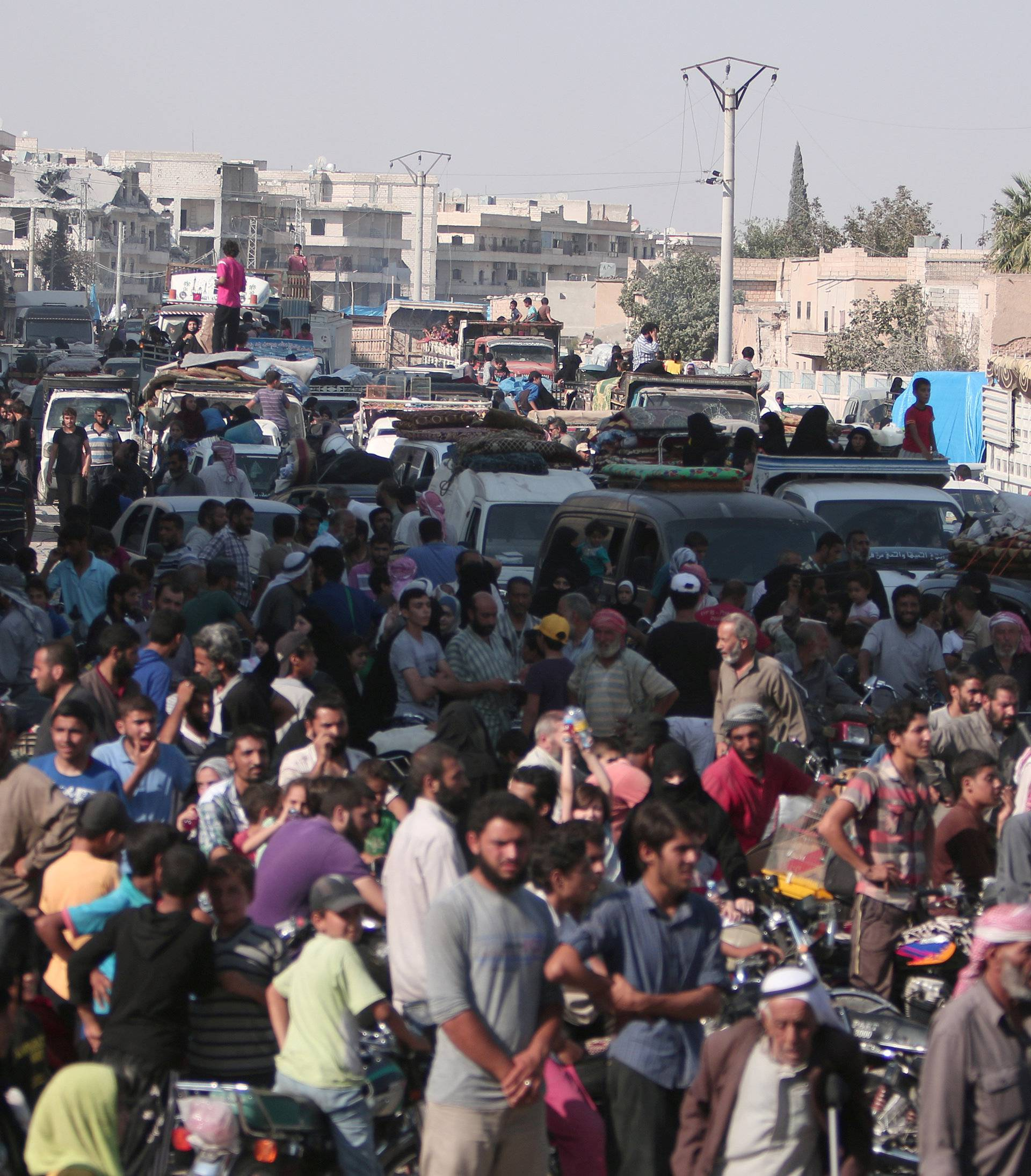 Civilians gather after they were evacuated by the Syria Democratic Forces (SDF) fighters from an Islamic State-controlled neighbourhood of Manbij