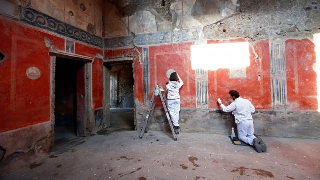 """Archaeologists work on  a fresco in the House of Lovers """"Casa degli Amanti\"""