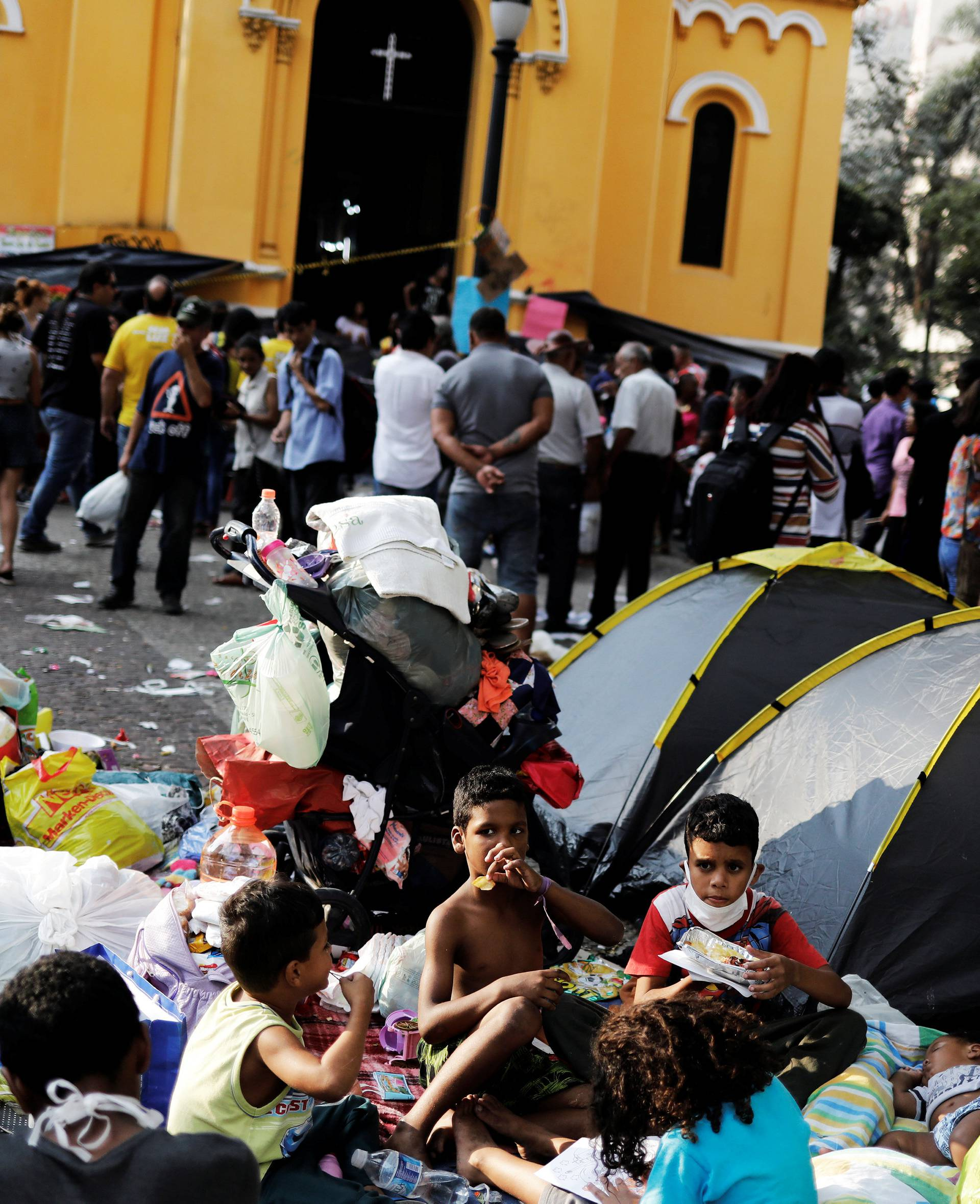 Children from homeless families that were living in the building that caught on fire, have lunch donated by well-wishers, next to a church at Largo do Painsandu Square in Sao Paulo