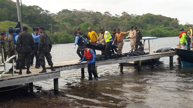 The remains of victims are recovered from the wreckage of a plane that crashed into the sea near the island of Roatan, Honduras