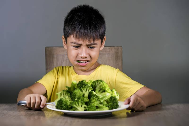 7 or 8 years old upset and disgusted Asian kid sitting on table in front of broccoli plate looking unhappy rejecting the fresh food in child hate green vegetables concept