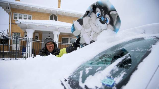 Francisco Sanchez wipes snow off his car with a boogie board before going out sledding with his kids in El Paso