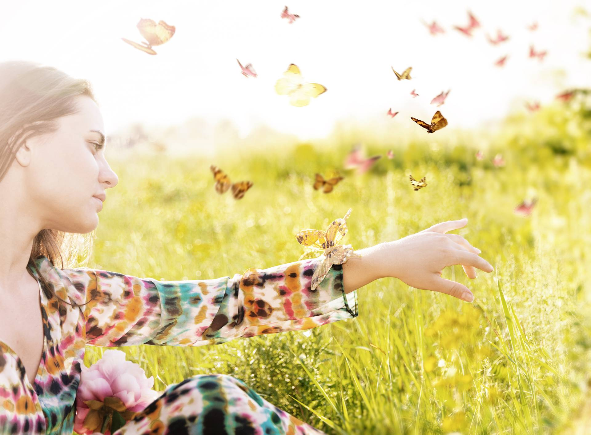 Girl sitting in a meadow in swarm of flitting butterflies.