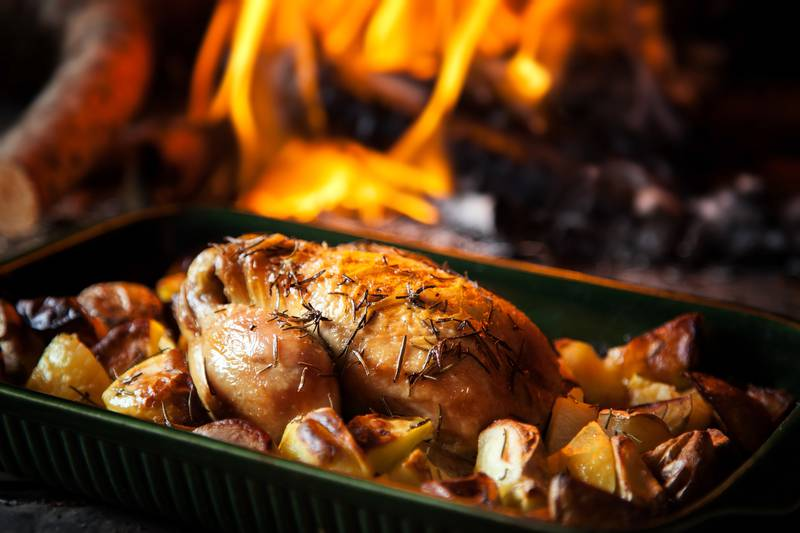 Roast chicken with potatoes with fiery background.
