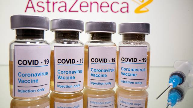 FILE PHOTO: Vials and medical syringe are seen in front of AstraZeneca logo in this illustration