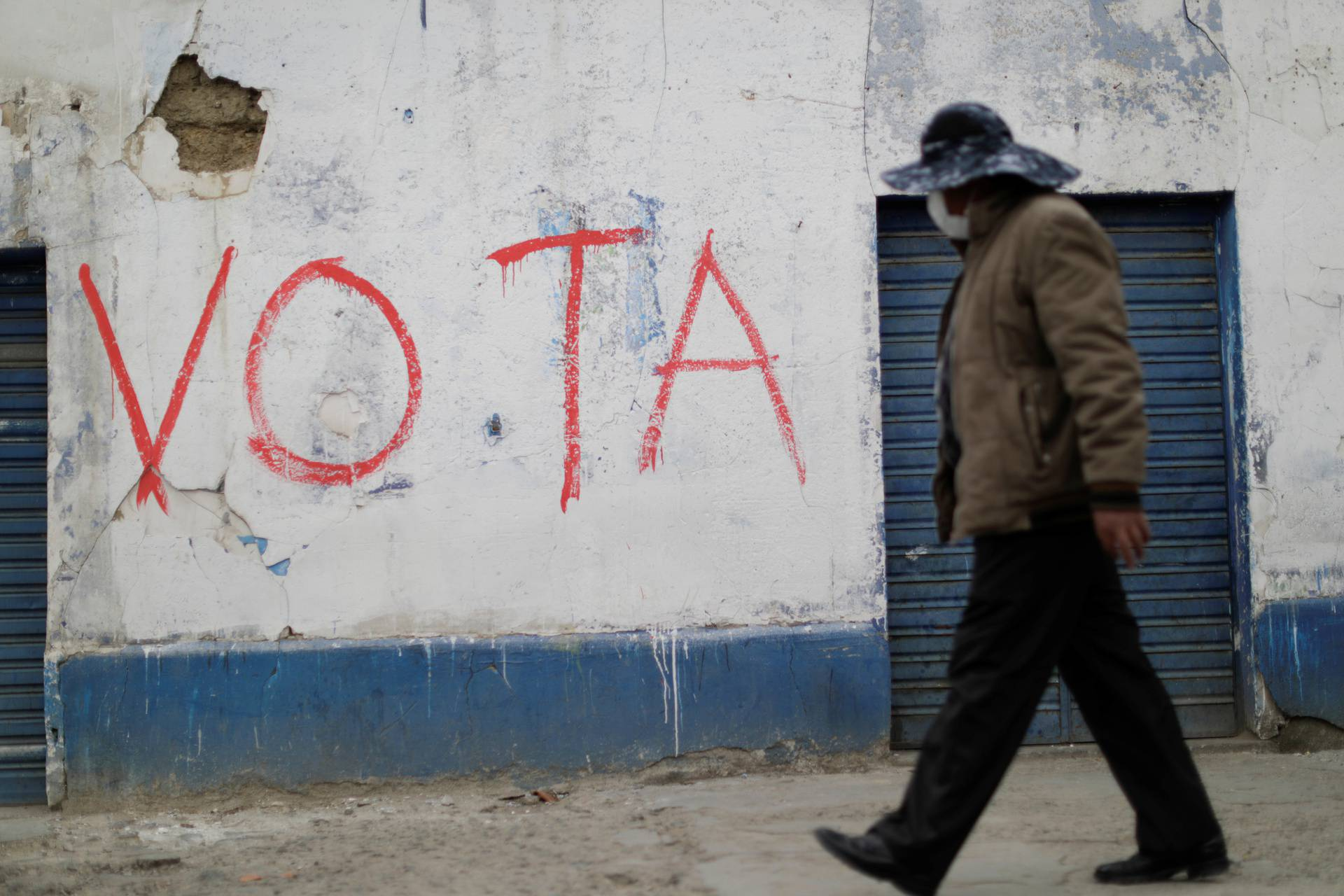 "A man walks past a graffiti reading ""Vote"" in El Alto"