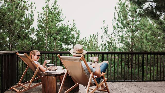 Young couple enjoying coffee on the balcony in the mountains