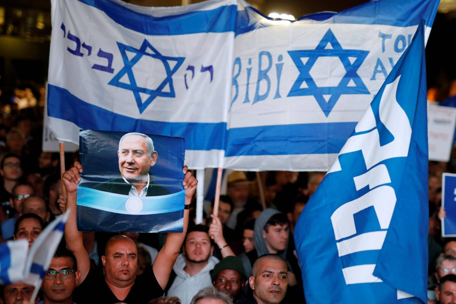 Supporters of Israeli Prime Minister Benjamin Netanyahu take part in a protest supporting Netanyahu after he was charged in corruption cases, in Tel Aviv, Israel
