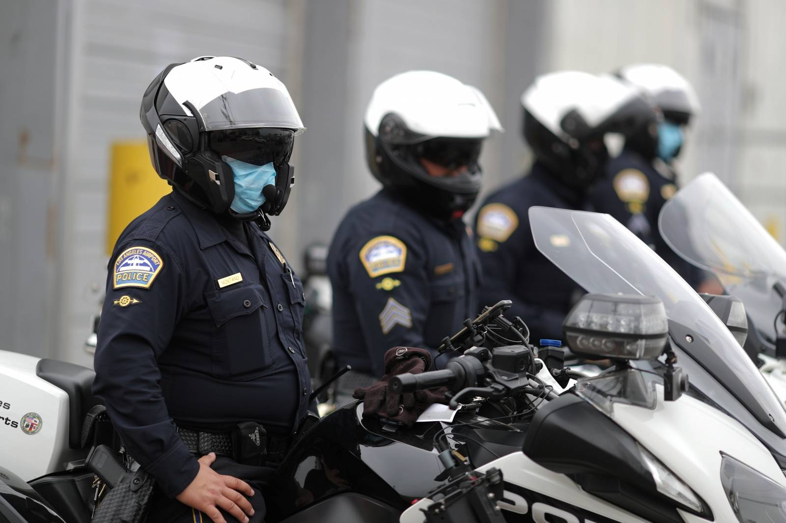 California Highway Patrol police officers wear masks as they watch hotel workers protesting outside airport hotels to demand healthcare coverage extension as the global outbreak of the coronavirus disease (COVID-19) continues, in Los Angeles