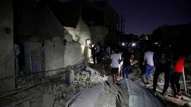 Civilians inspect the site of a car bomb attack in Sadr City district of Baghdad