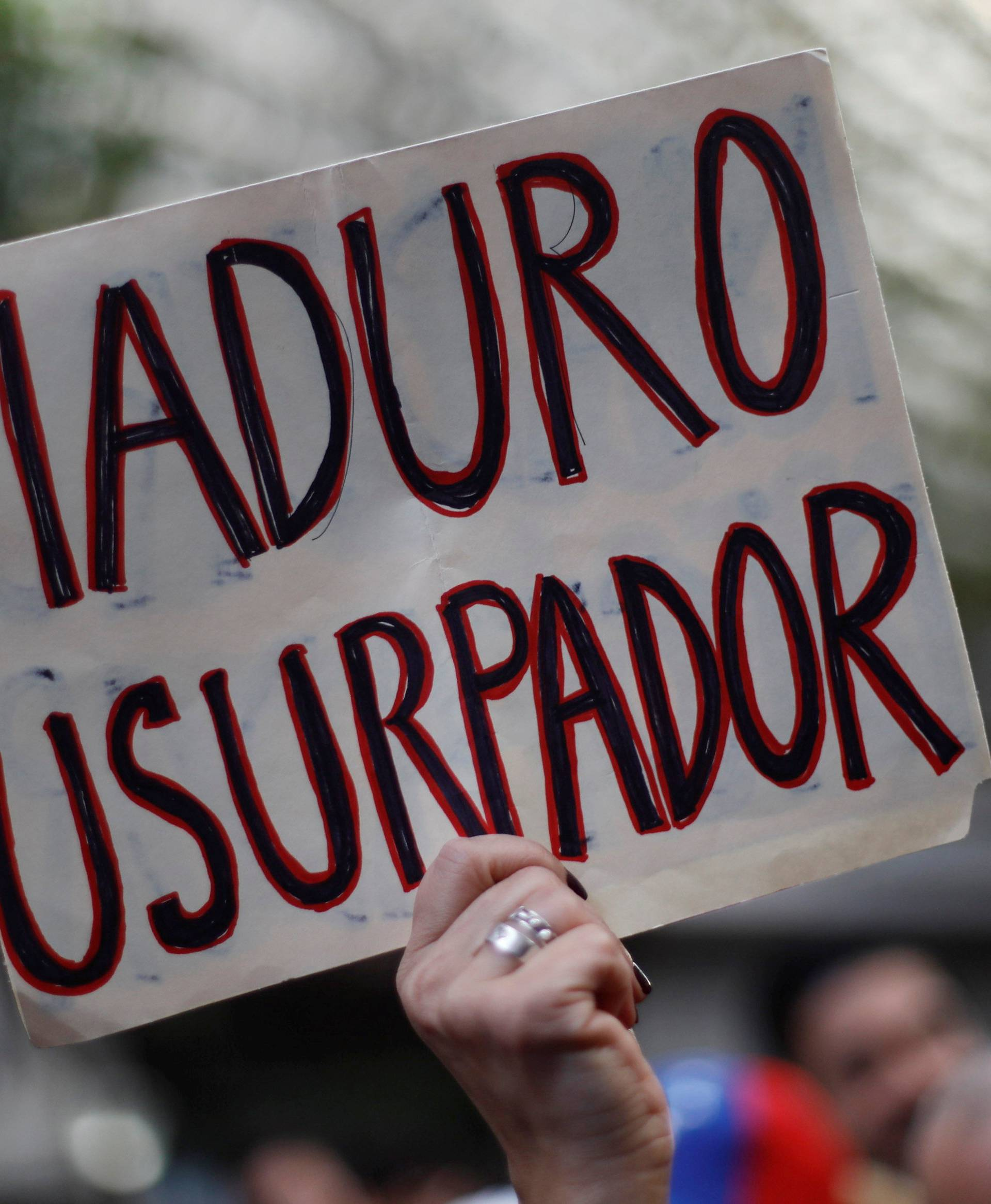 A woman holds a sign as she gathers in support of Venezuela's opposition leader Juan Guaido outside the Embassy of Venezuela in Mexico City