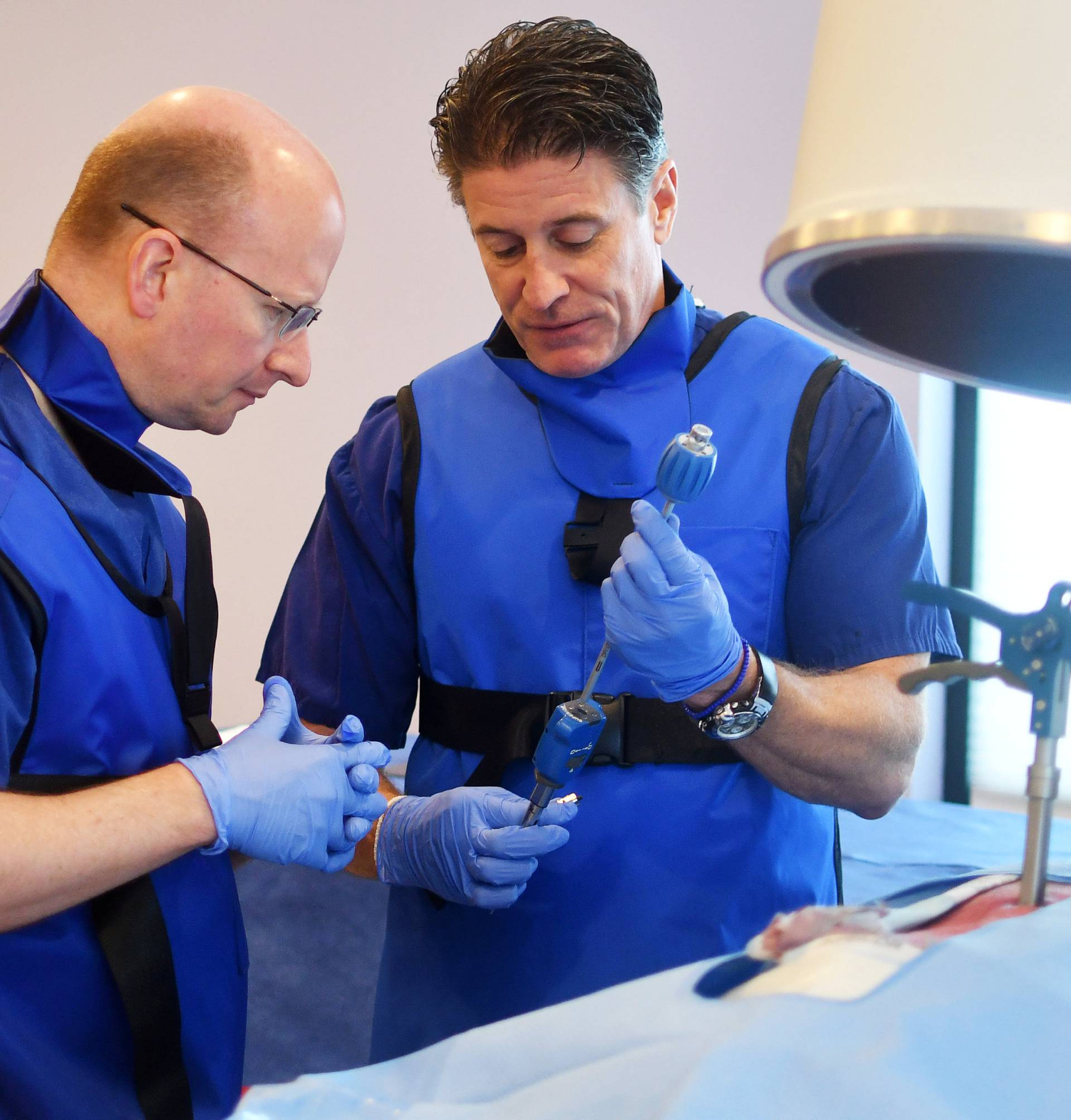 Drew Gaworski, an instructor for medical device maker Vertiflex, uses a donated human spine to teach Dr. Richard Stayner, (L), how to implant a device during a seminar in Sterling