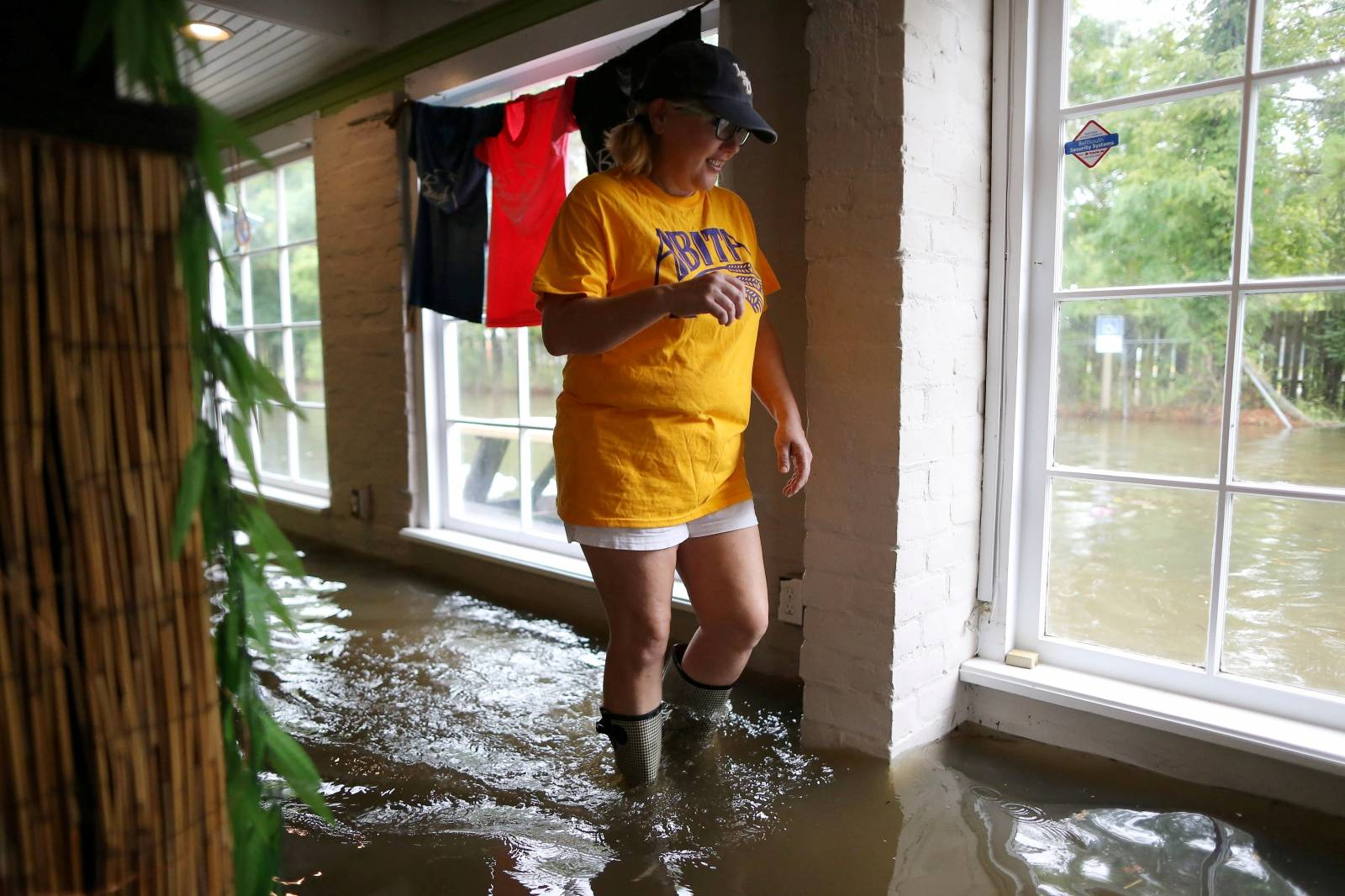 Robyn Iacona-Hilbert walks through her flooded business after Hurricane Barry in Mandeville