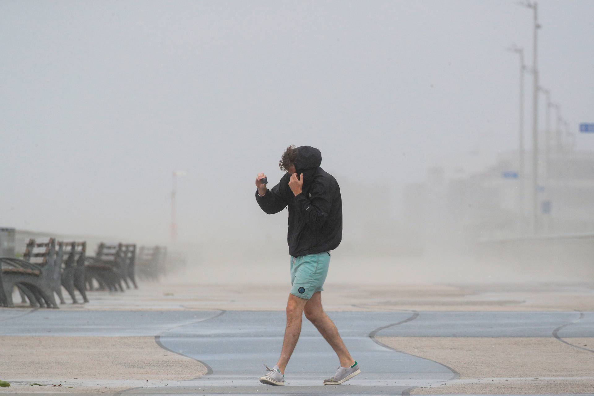 A man shields himself from the winds from Tropical Storm Isaias while walking on the boardwalk in the Rockaway area of Queens in New York