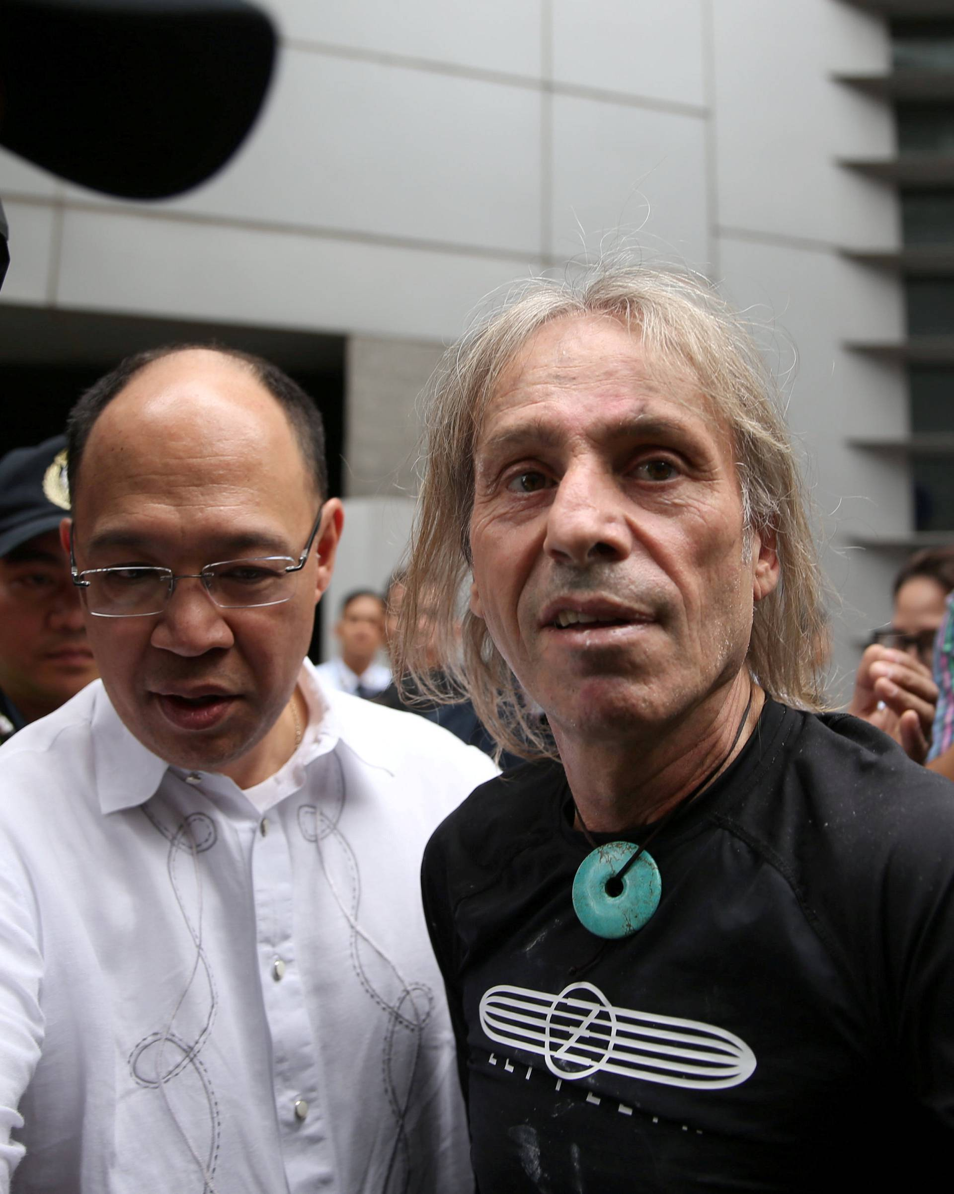 French climber Robert is escorted by Filipino cops after his 47-storey GT International Tower climb in Makati City