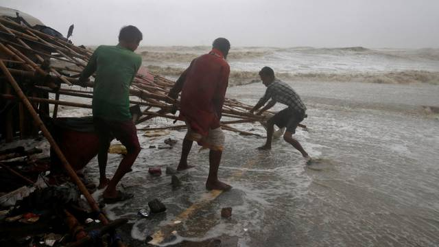 Men remove bamboo rooftop of a stall damaged by heavy winds at a shore ahead of Cyclone Yaas in Bichitrapur