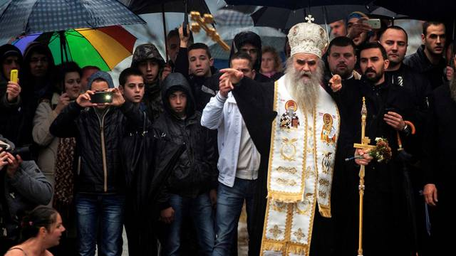 FILE PHOTO: Metropolitan Amfilohije Radovic throws a wooden cross in the Ribnica River during Epiphany Daycelebrations in Podgorica. Montenegro