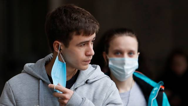 People wearing protective face masks walk in a street amid the outbreak of the coronavirus disease in Moscow