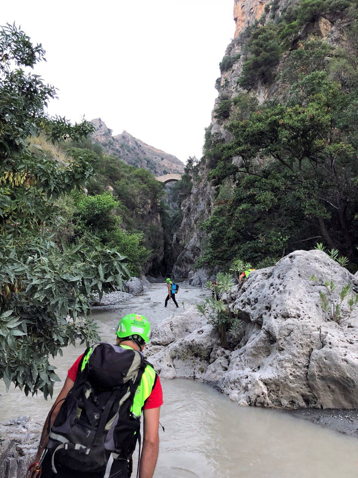 Alpine rescue workers cross the canyon of the river Raganello as they search the area after several people were killed in a mountain gorge flooding, in the municipality of Civita