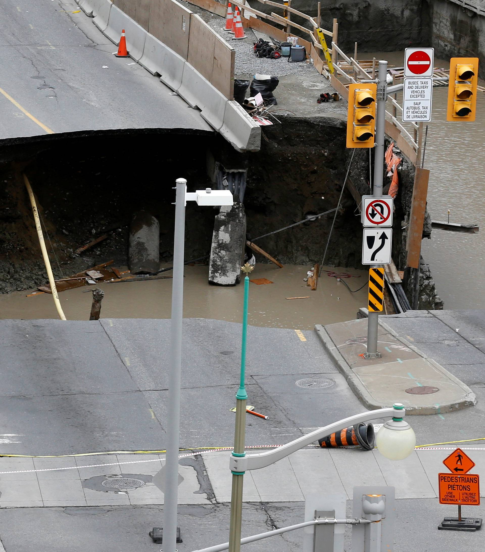 Workers look at a large sinkhole in Ottawa