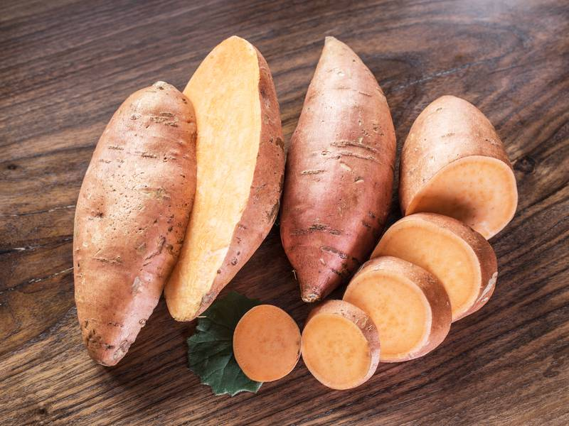 Sweet potatoes on the old wooden table.