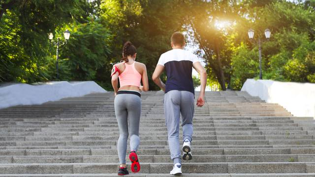Couple jogging outside, runners training outdoors working out in