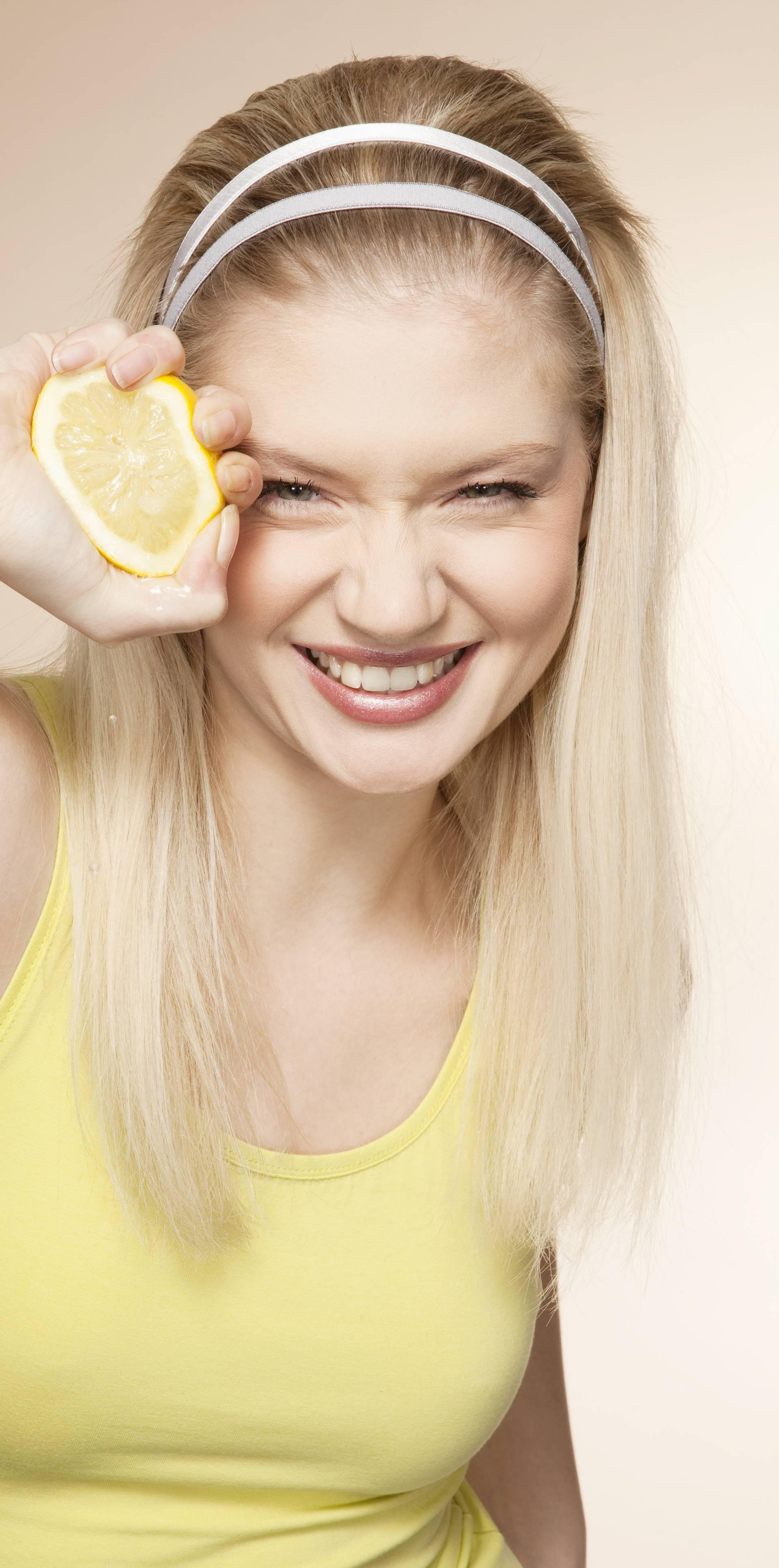 Young woman squeezing lemon, studio shot