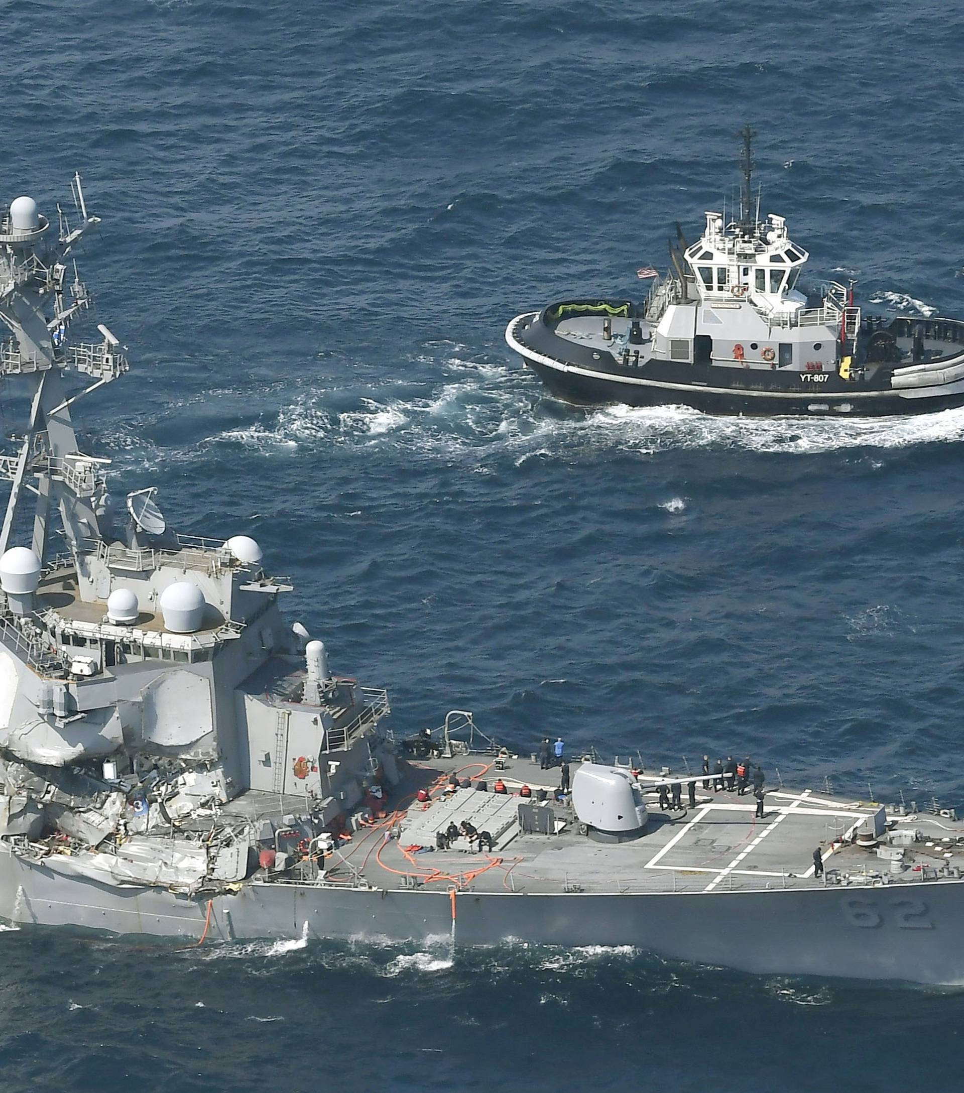The Arleigh Burke-class guided-missile destroyer USS Fitzgerald, damaged by colliding with a Philippine-flagged merchant vessel, is seen next to a tugboat off Shimoda, Japan